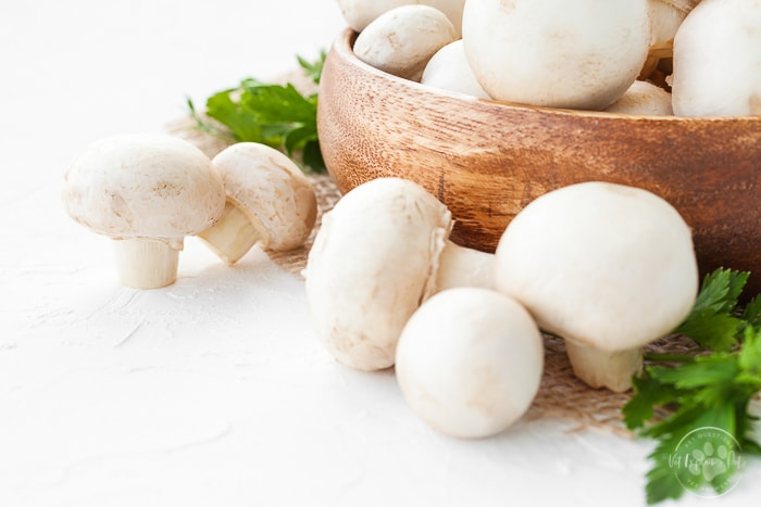 white button mushrooms in basket on countertop