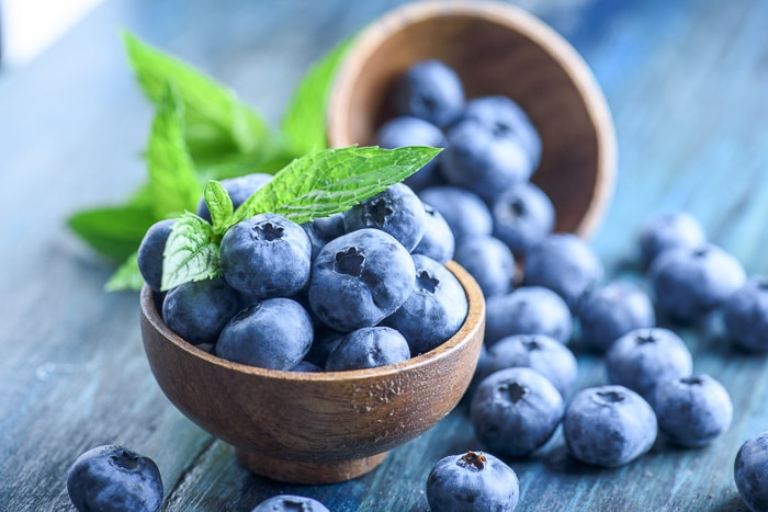 fresh blueberries in wooden bowl with blue background