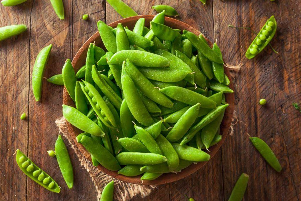 fresh sugar snap peas in wooden bowl