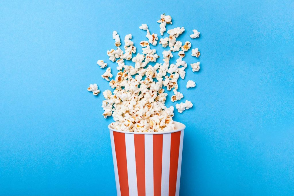 movie popcorn in red and white carton on blue background