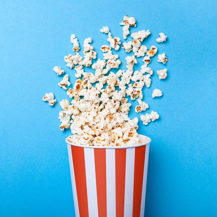 movie theater popcorn in red and white striped carton on blue background