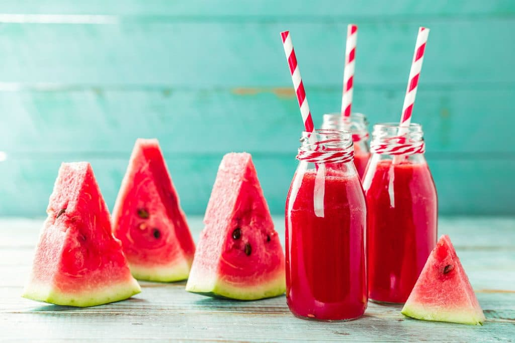 watermelon slices with watermelon juice in glasses with red and white striped straws