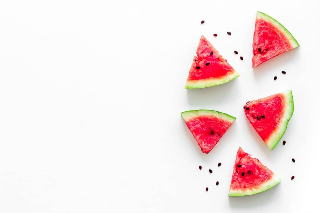 red watermelon triangles laid out on white background wih seeds