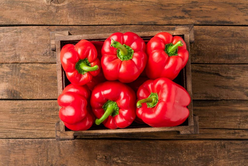 red bell peppers in wooden basket on wooden table