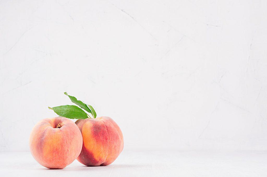 two ripe peaches on white table