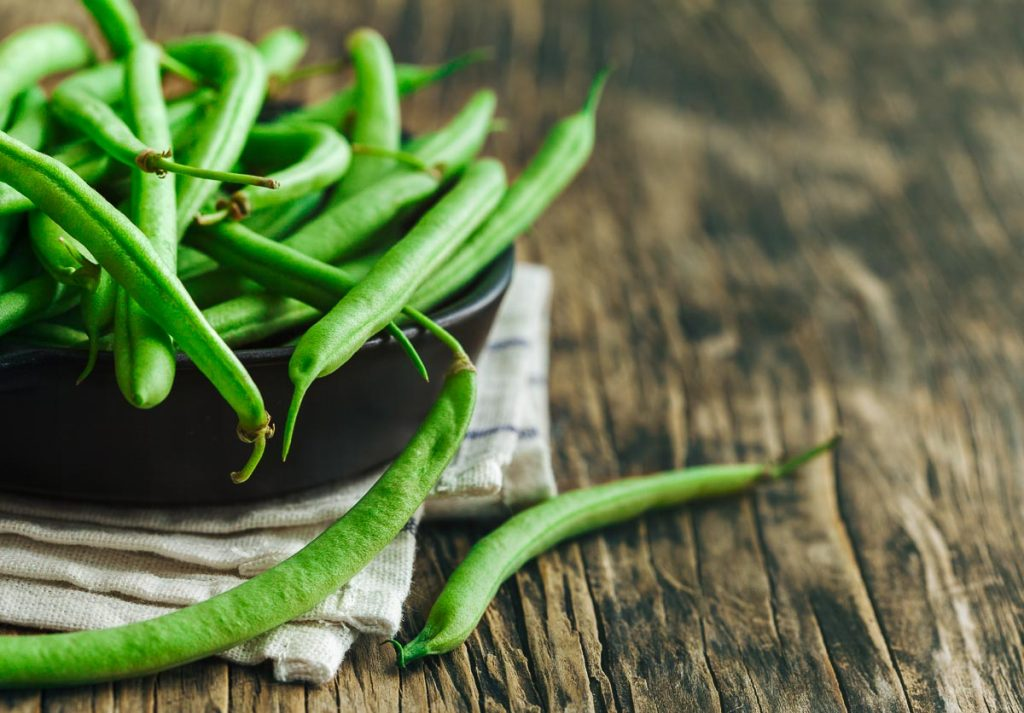closeup of green beans in black pan on wooden table