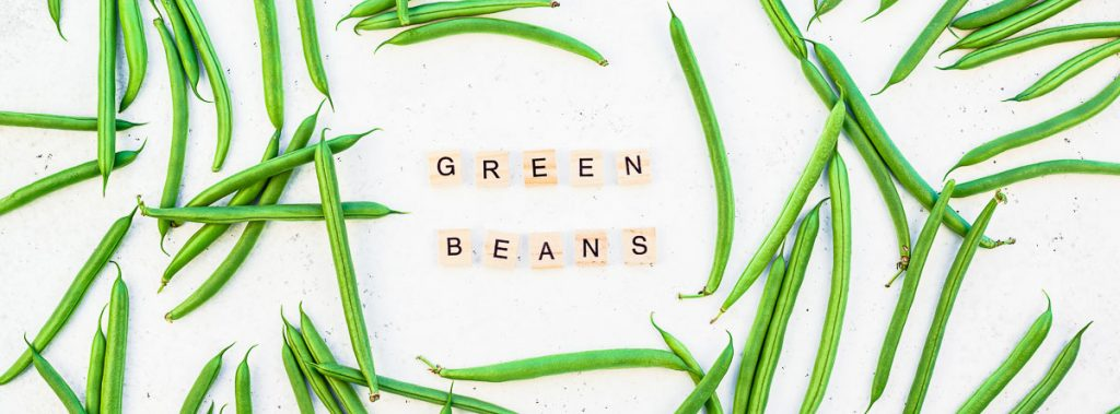 green beans spread out on white background with scrabble letters