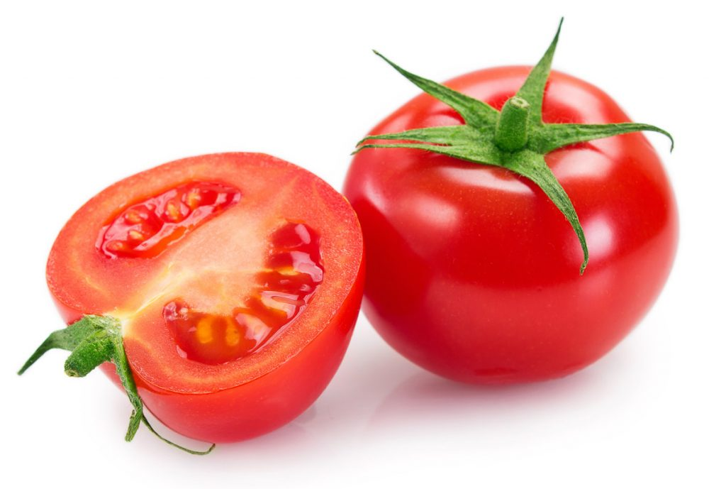 two red tomatoes split in half on white background