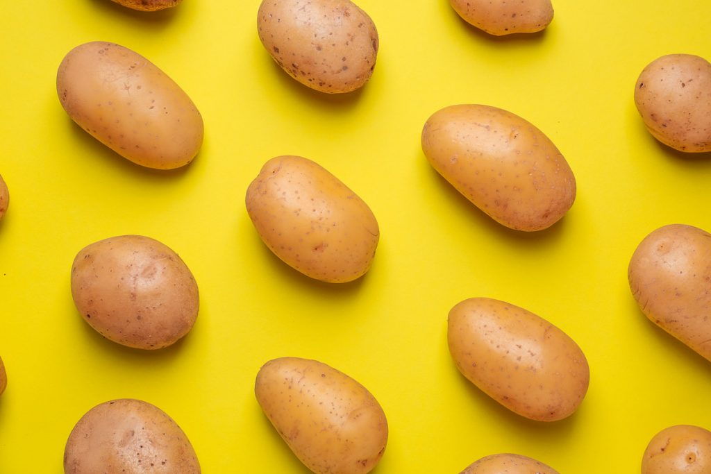 russet potatoes evenly spaced on yellow background